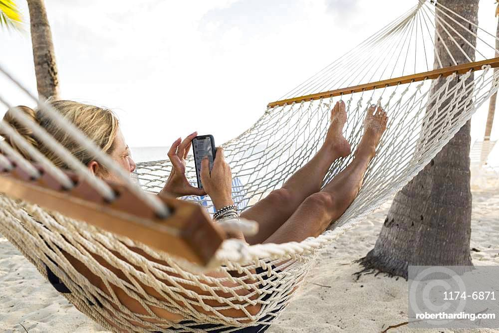 Woman in hammock using her smart phone, Grand Cayman, Cayman Islands