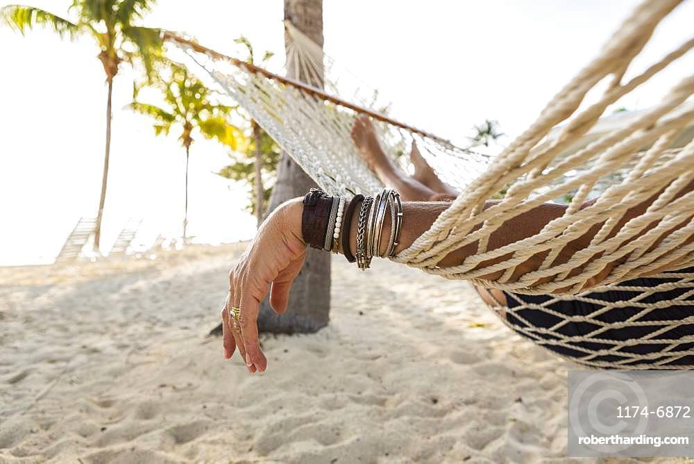 Close up of woman's arm and bracelets, relaxing resting in hammock , Grand Cayman, Cayman Islands