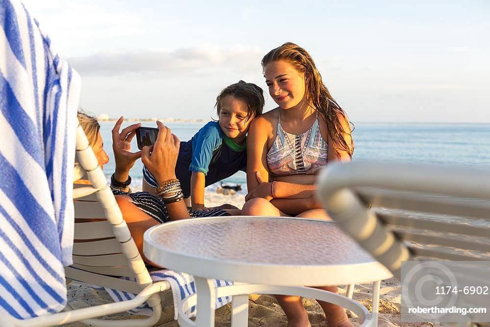 Mother and her children enjoying the beach at sunset, Grand Cayman, Cayman Islands