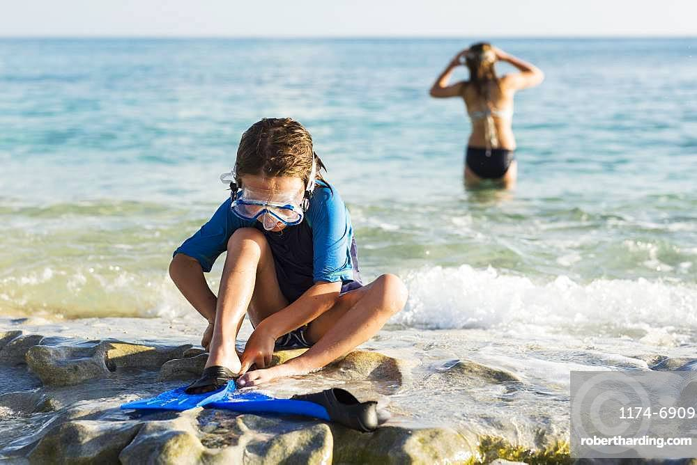 5 year old boy putting his swim fins on at the beach, Grand Cayman, Cayman Islands