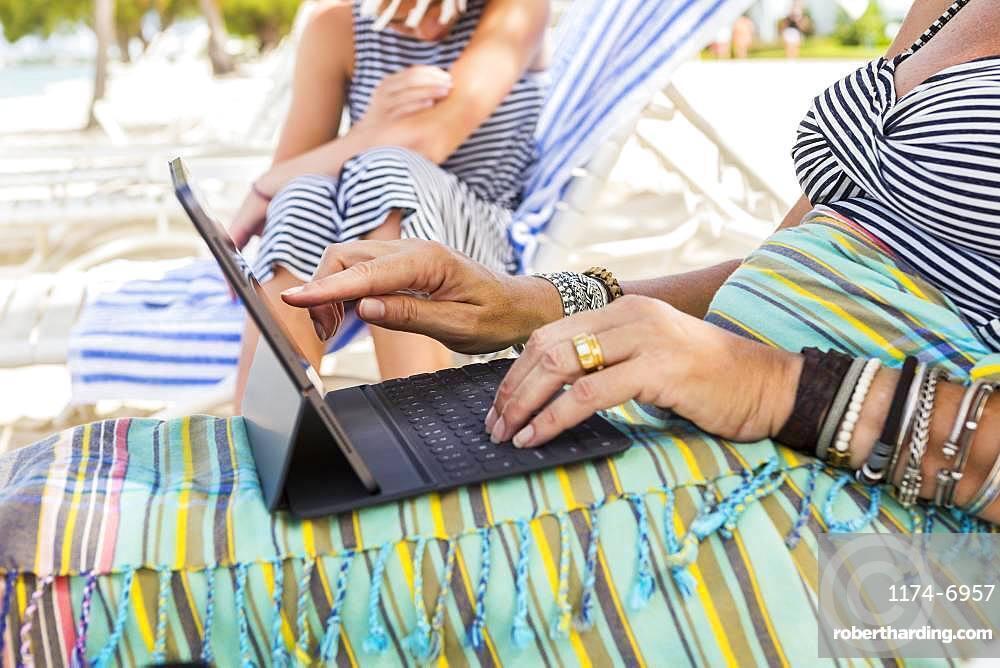 adult woman executive using laptop on the beach , Grand Cayman, Cayman Islands