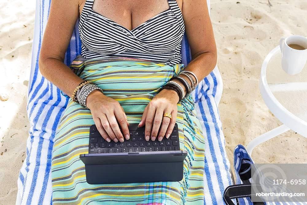 adult woman executive using laptop on the beach, Grand Cayman, Cayman Islands