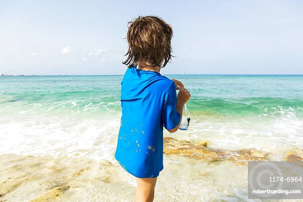 5 year old boy preparing to wear snorkelling mask, Grand Cayman, Cayman Islands