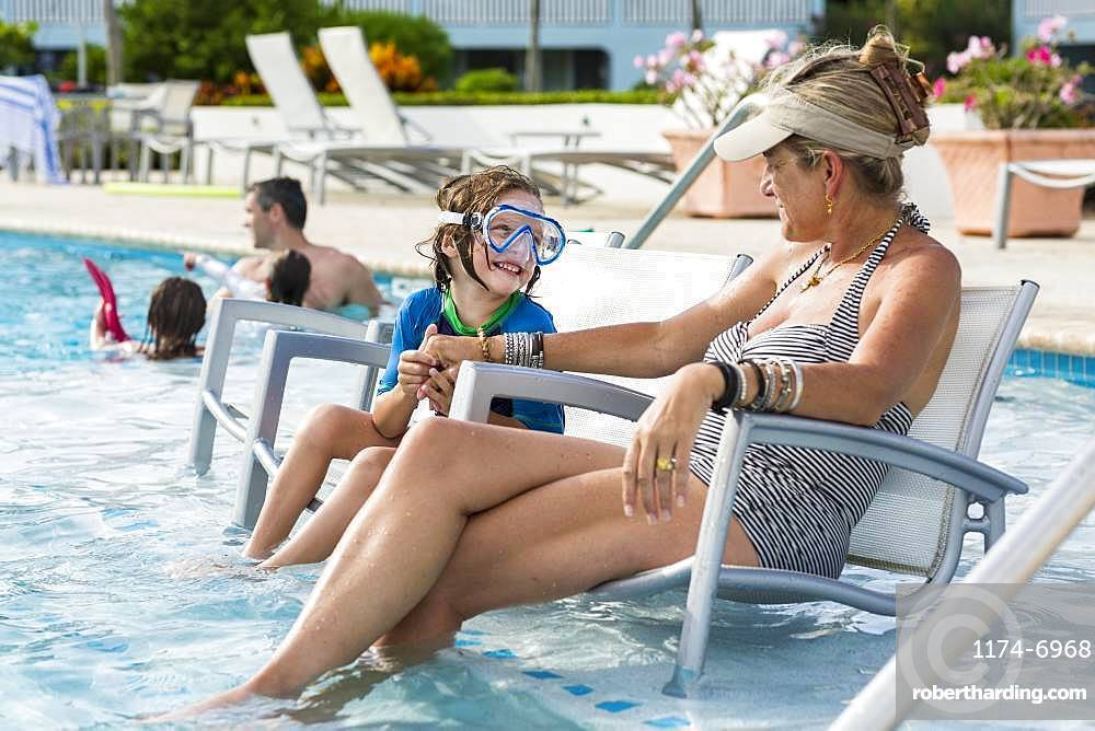 mother and her 5 year old son talking by the pool, Grand Cayman, Cayman Islands