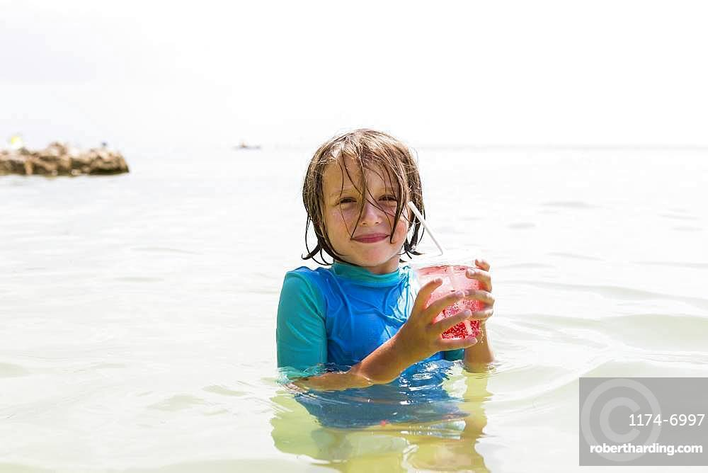smiling 5 year old boy in the ocean, holding a fruit drink, Grand Cayman, Cayman Islands