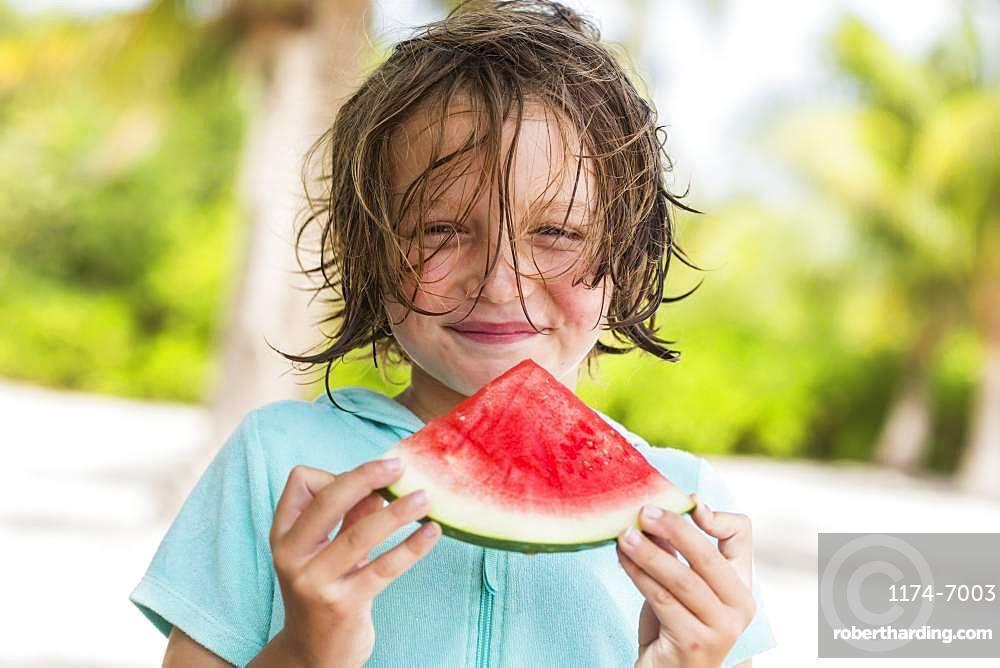 Smiling 5 year old boy eating watermelon slice, Grand Cayman, Cayman Islands
