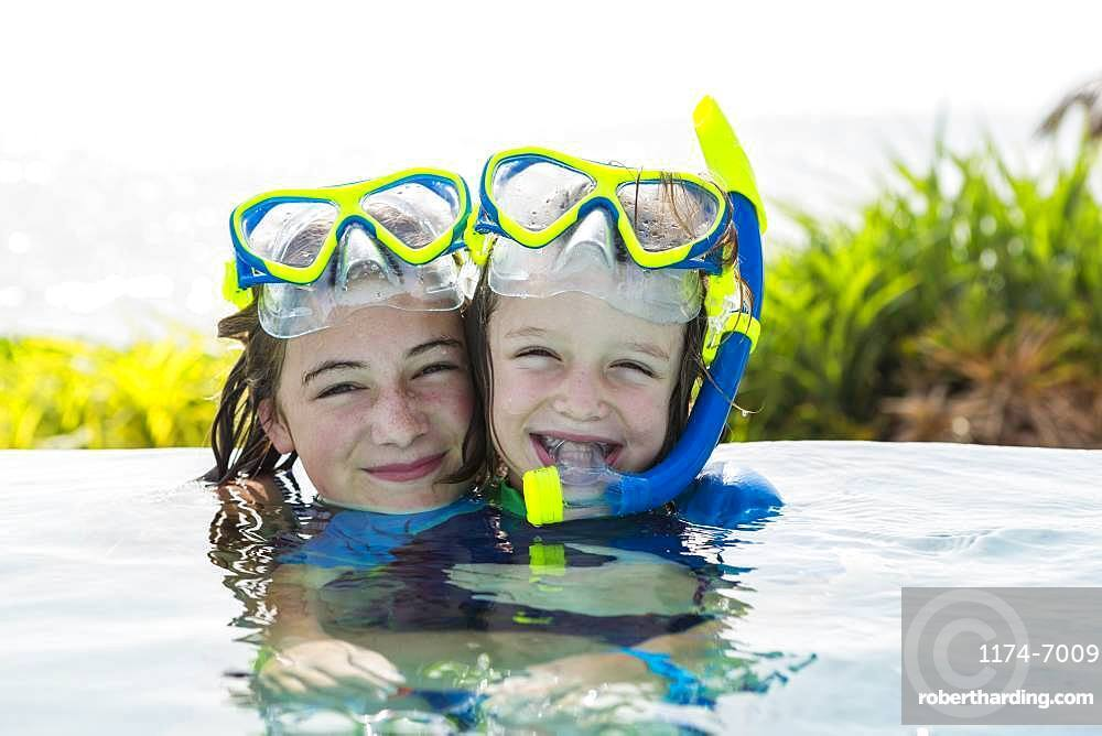 A teenage girl and her 5 year old brother in pool, smiling, Grand Cayman, Cayman Islands