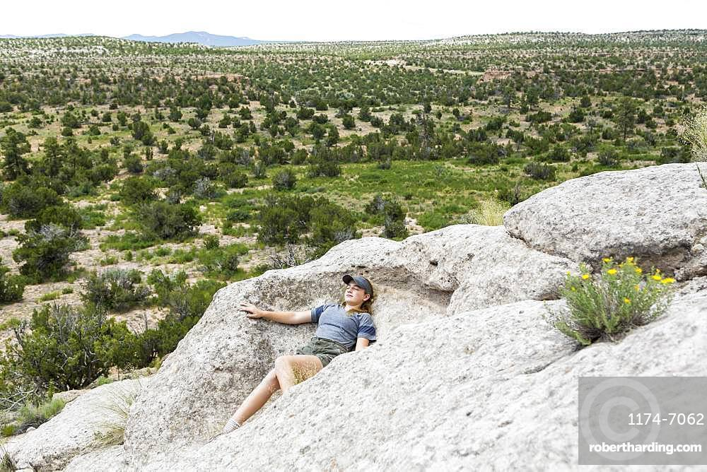 A teenage girl lying down on rock formation at a desert site