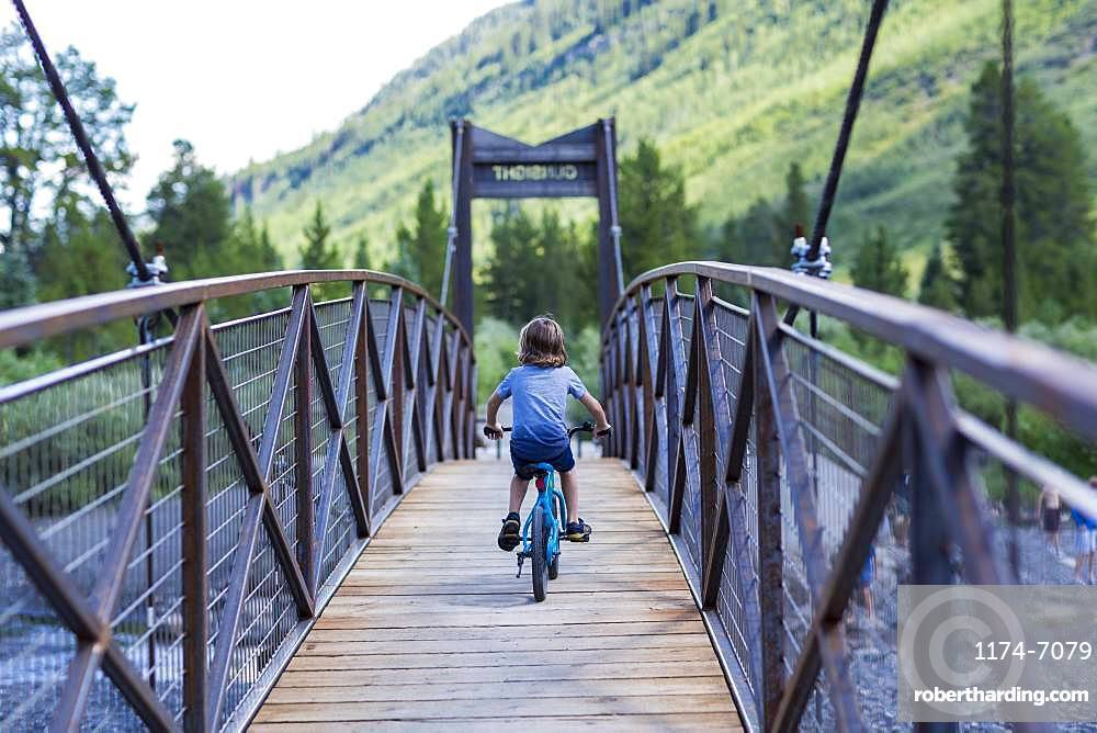rear view of 5 year old boy on mountain crossing narrow bridge