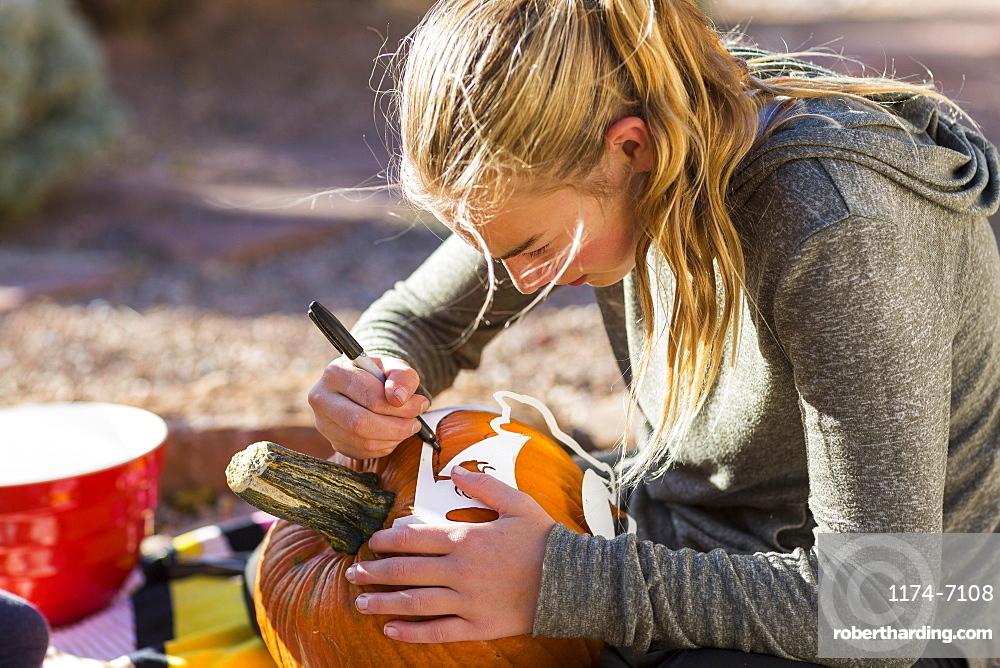 A teenage girl carving pumpkin outdoors at Halloween