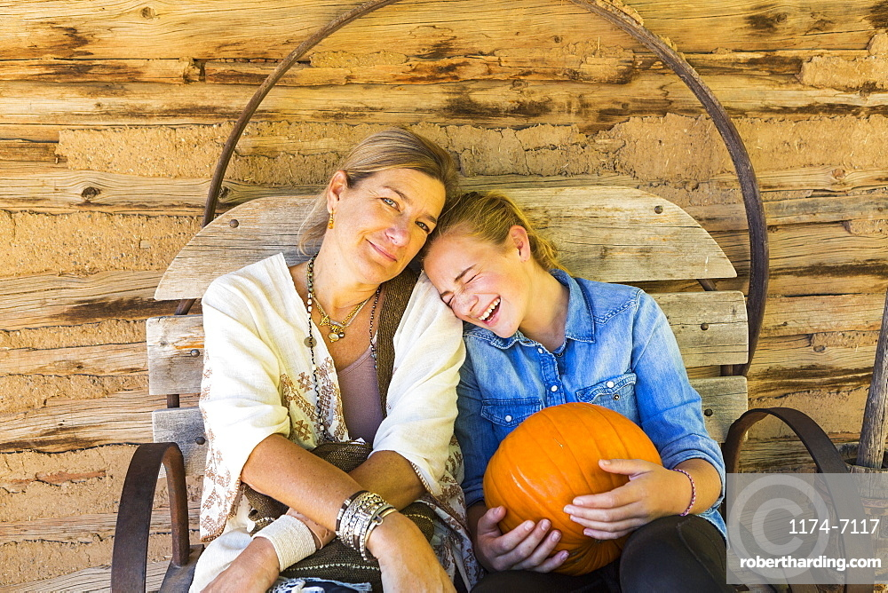portrait of mother and her teen age daughter holding pumpkin