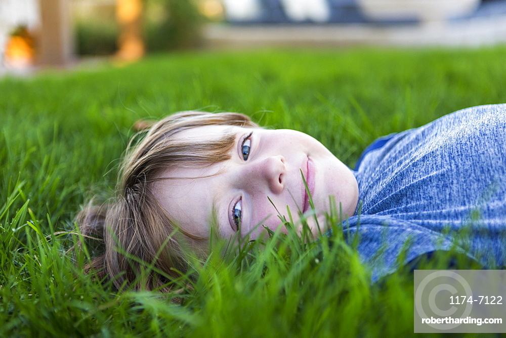portrait of smiling Six year old boy lying down in green grass