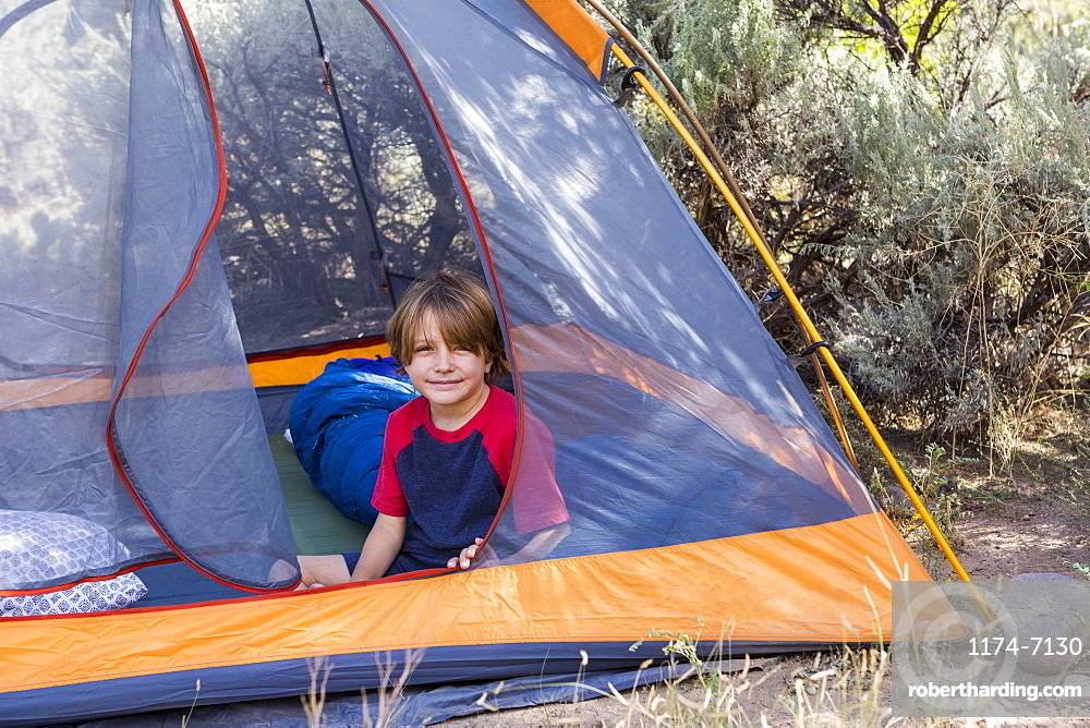 portrait of Six year old boy sitting in a tent