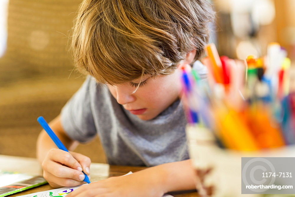 Six year old boy drawing amoung colorful pens