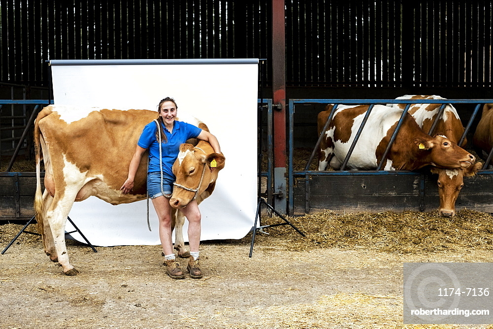 Portrait of female farmer standing in front of a barn with a Guernsey cow