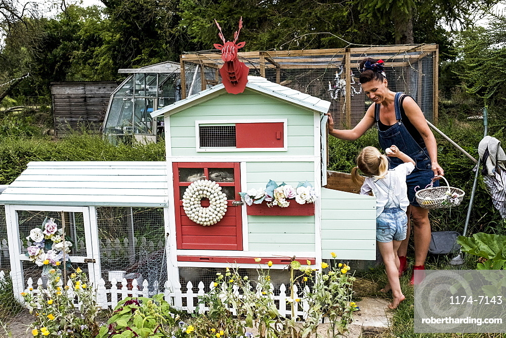 Smiling woman and girl standing in a garden next to a colourful hen house