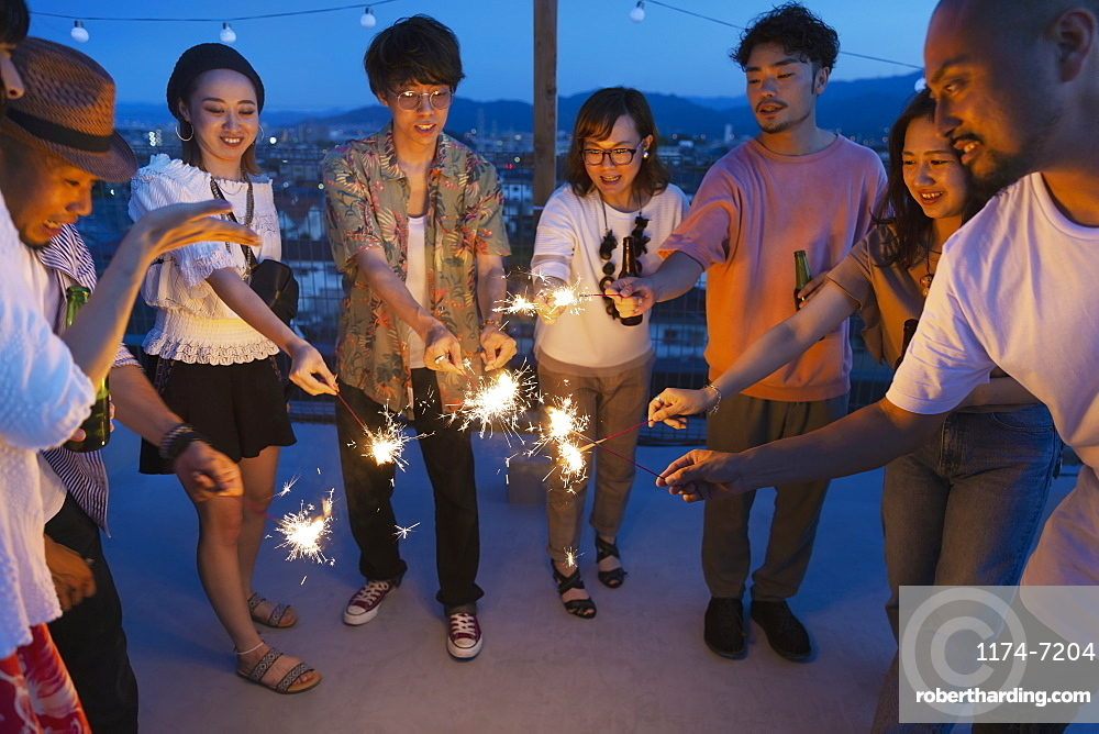 Group of young Japanese men and women with sparklers on a rooftop in an urban setting, Fukuoka, Kyushu, Japan