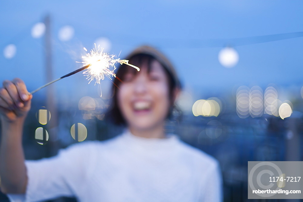 Smiling young Japanese woman holding sparkler on a rooftop in an urban setting, Fukuoka, Kyushu, Japan