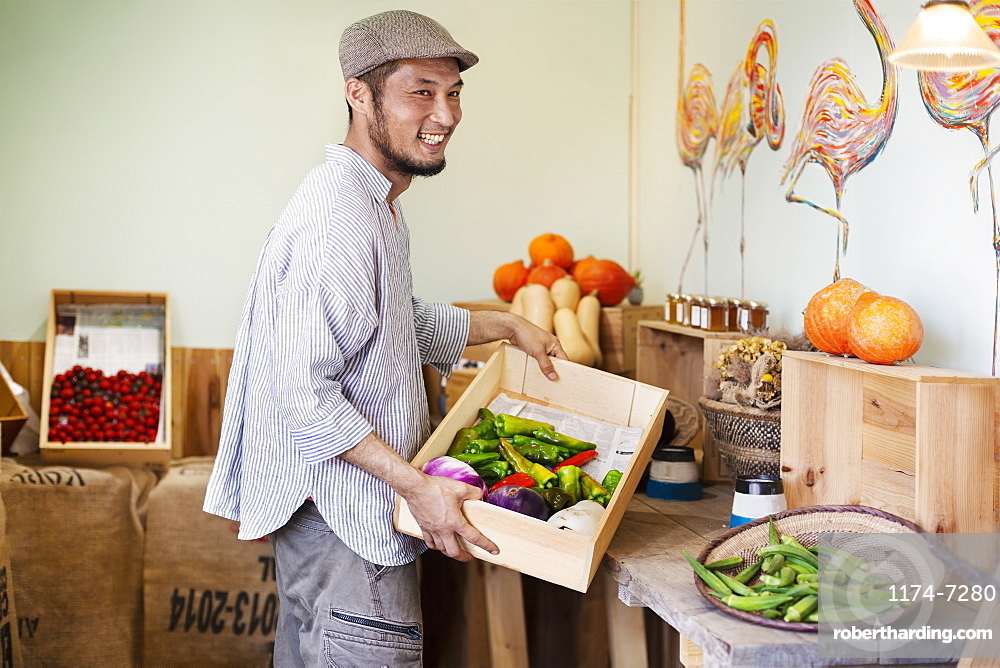 Smiling Japanese man wearing cap standing in farm shop, holding crate with fresh vegetables, Kyushu, Japan