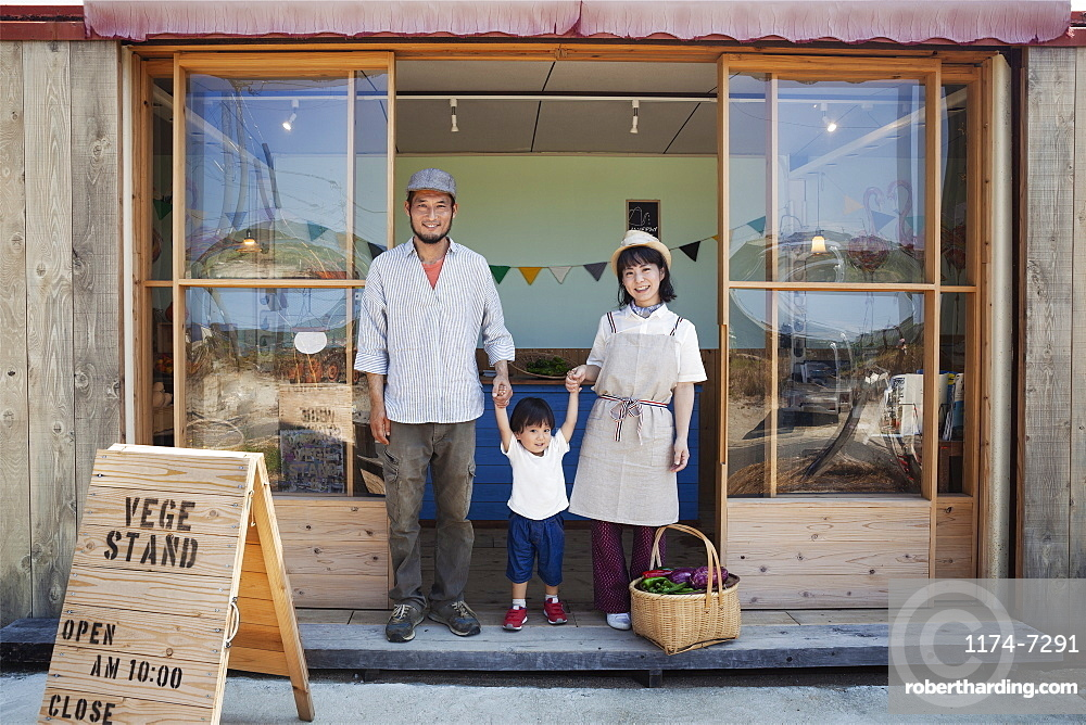 Japanese man, woman and boy standing outside a farm shop, holding hands, looking at camera, Kyushu, Japan