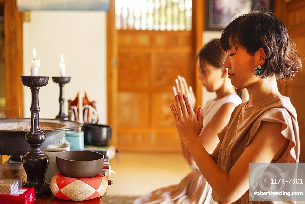 Two Japanese women kneeling in Buddhist temple, praying, Kyushu, Japan