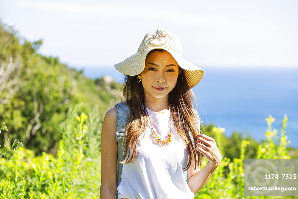 Japanese woman wearing hat standing on a cliff, ocean in the background, Kyushu, Japan