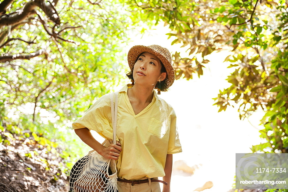 Japanese woman wearing hat hiking in a forest, Kyushu, Japan