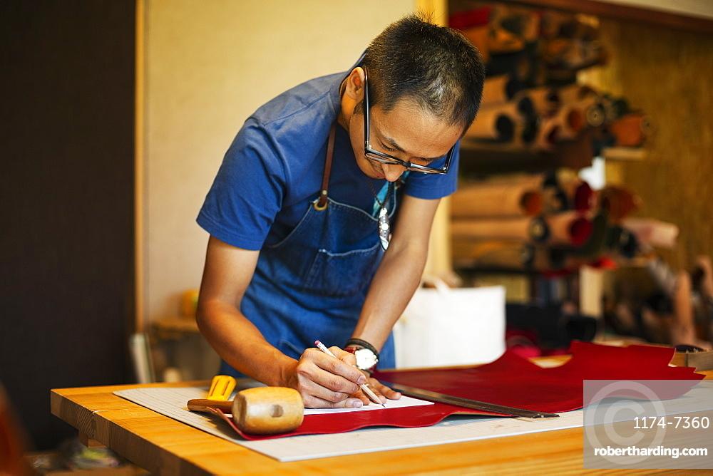 Japanese man wearing blue apron working in a leather shop, Kyushu, Japan