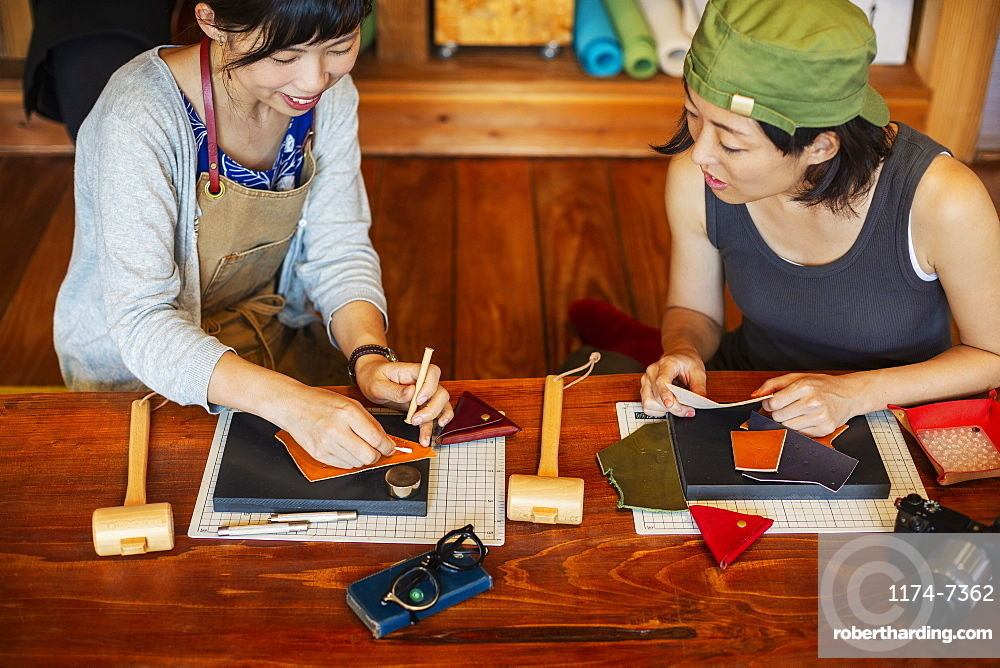 High angle view of two Japanese women sitting at a table, working in a leather shop, Kyushu, Japan