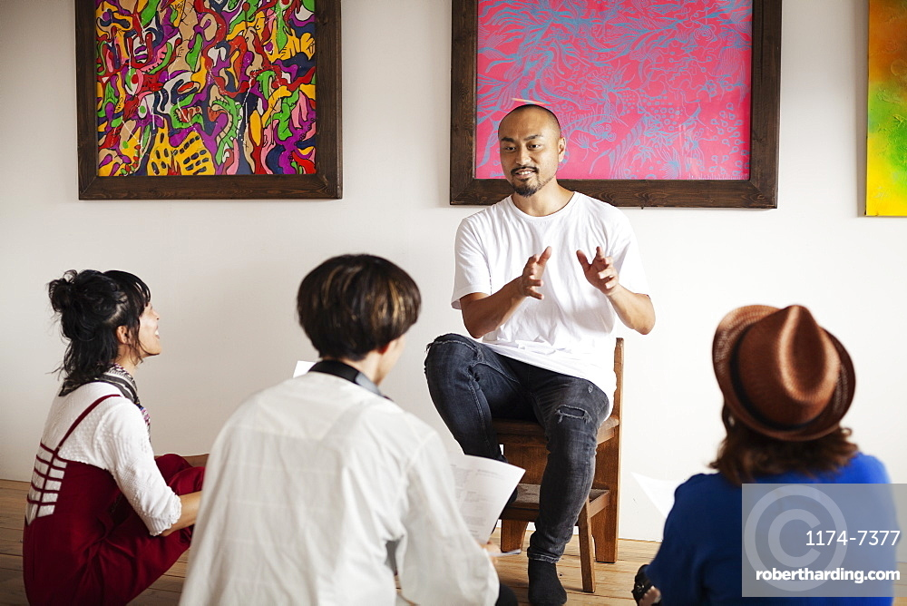 Group of Japanese men and women sitting in art gallery, holding a discussion, Kyushu, Japan