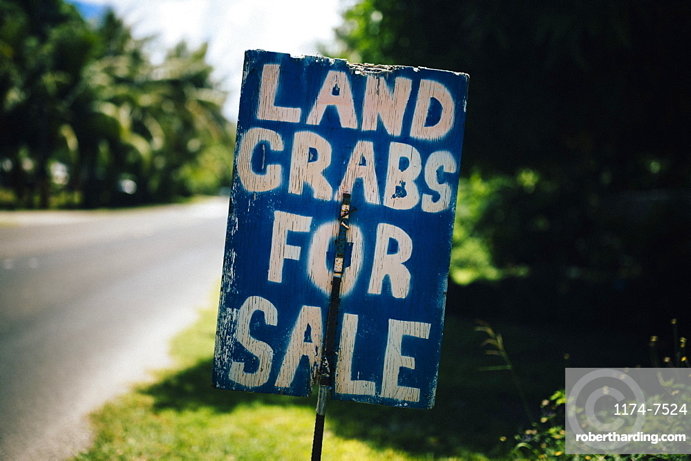 Handwritten sign by the side of road advertising land crabs for sale, Guam