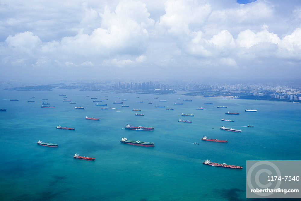 High angle view of barges and cargo ships in a bay, cityscape in the distance, Singapore