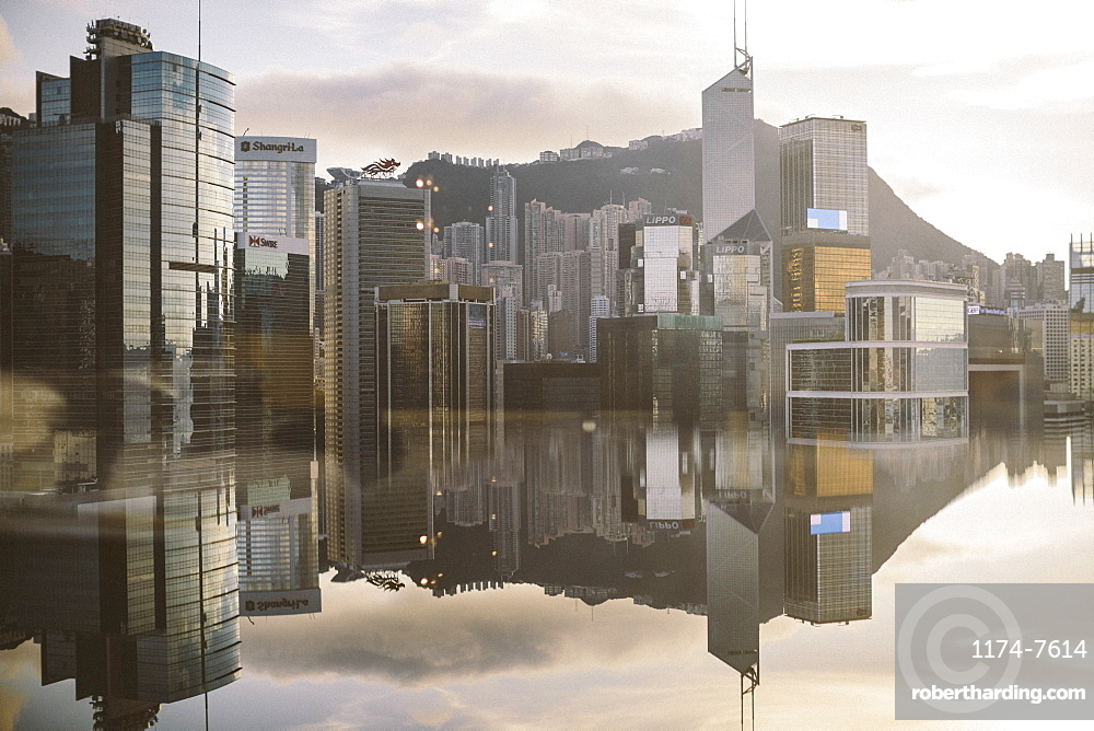 Cityscape with modern skyscrapers reflected in calm sea, China