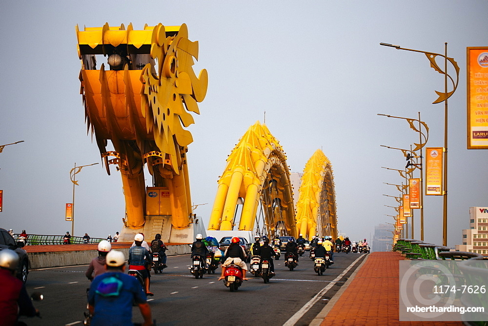 Rear view of commuters on motorcycles crossing bridge in the shape of a dragon, Vietnam