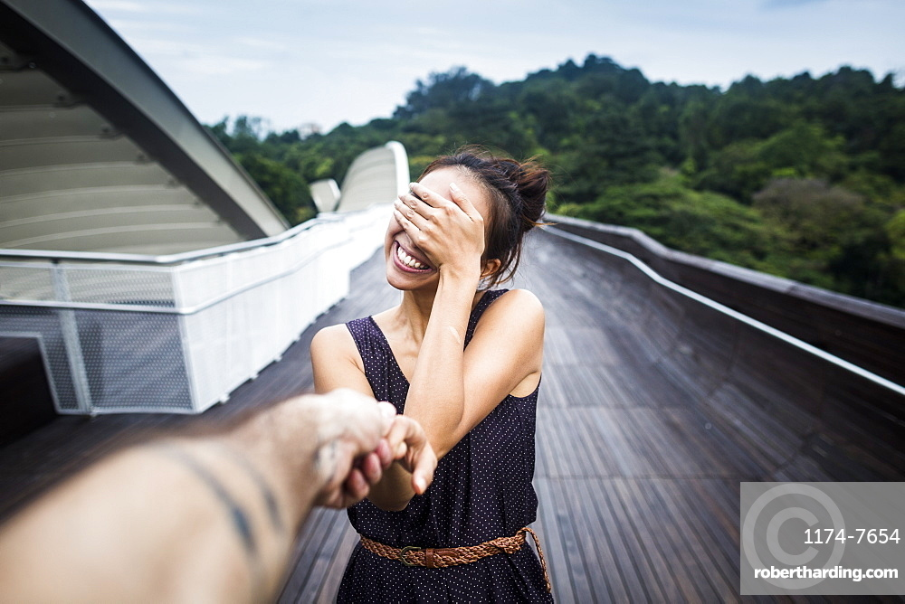 Smiling young woman standing on a bridge, covering her face, holding man's hand, Singapore
