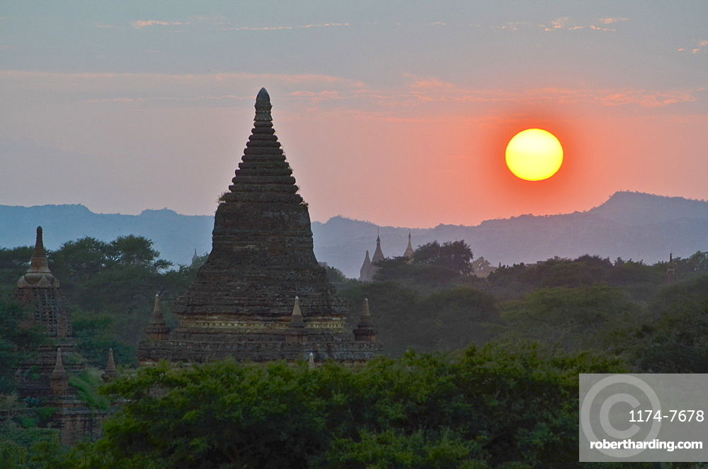 Sunset over distant mountains with stupa of temple in the foreground, Bagan, Myanmar