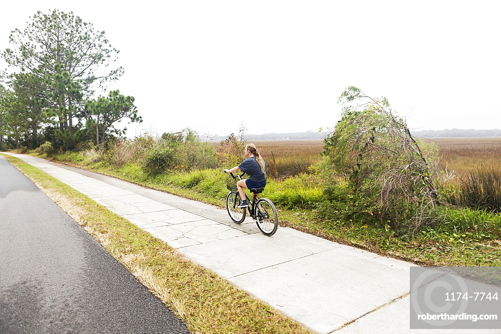 Teenage girl riding a bicycle along a path on open ground by water, St Simon's Island, Georgia, United States