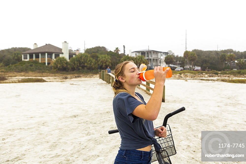 Teenage girl drinking water from a bottle, St Simon's Island, Georgia, United States