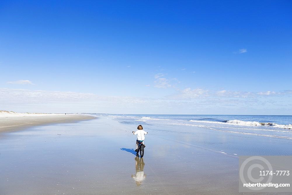 A young boy biking on a sandy beach, St Simon's Island, Georgia, United States