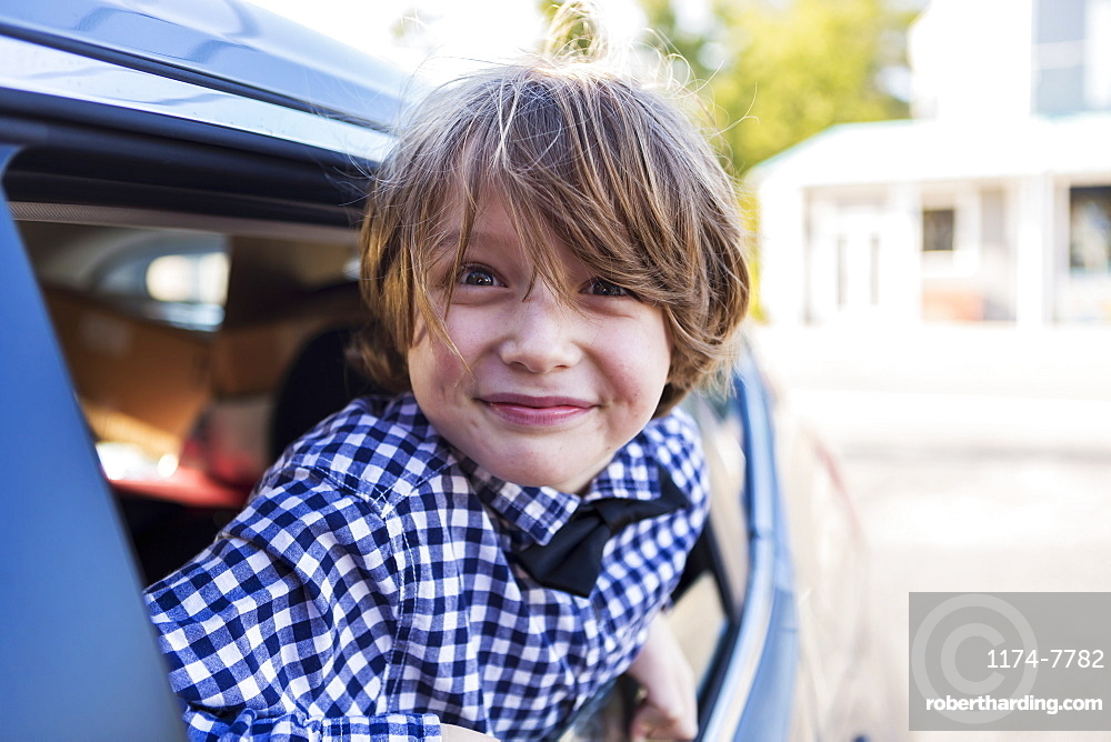 A six year old boy smiling at camera, looking out of car window, St Simon's Island, Georgia, United States