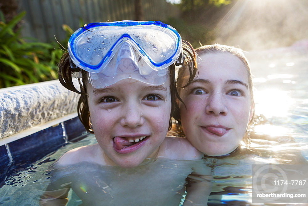A teenage girl and brother in a warm pool, looking at the camera, sticking their tongues out, St Simon's Island, Georgia, United States