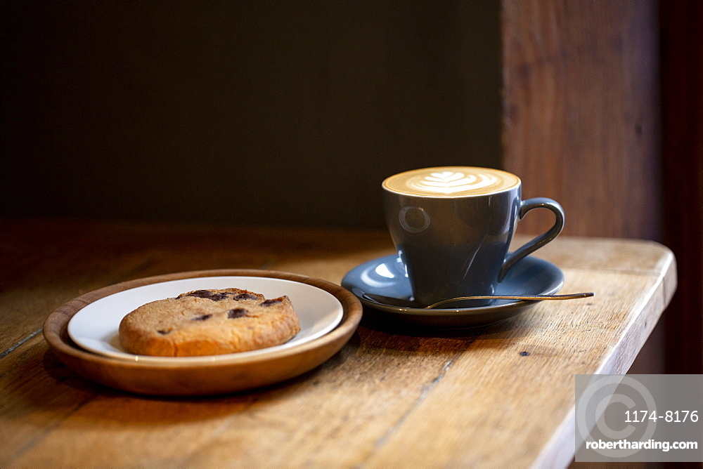 Close up of cup of Cappuccino and chocolate chip cookie on a plate in a cafe