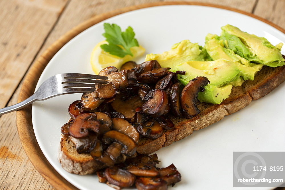 High angle close up of Chestnut mushrooms and avocado on toasted sourdough bread on a plate