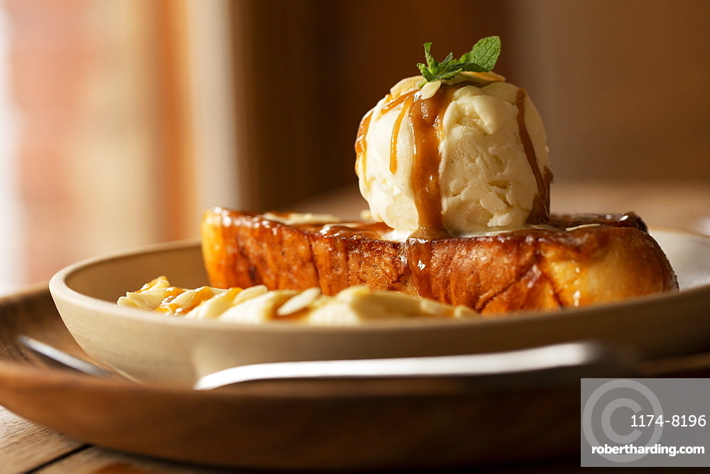 Close up of French toast with sliced banana and ice cream in a cafe