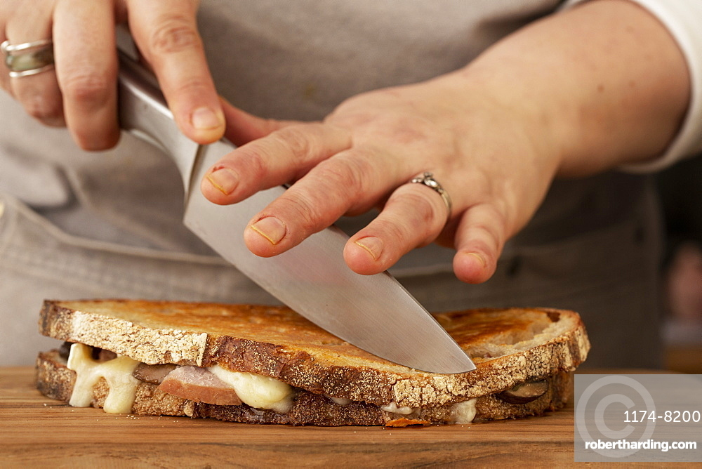 Close up of person slicing toasted sourdough cheese melt with chef's knife