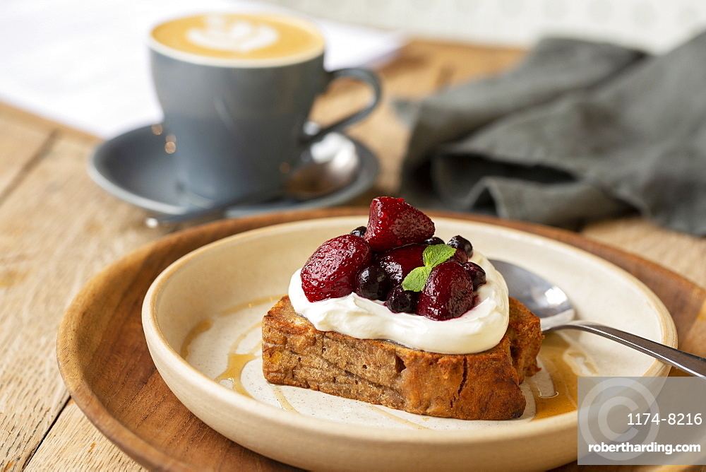 High angle close up of banana bread topped with yoghurt and mixed berries in a cafe