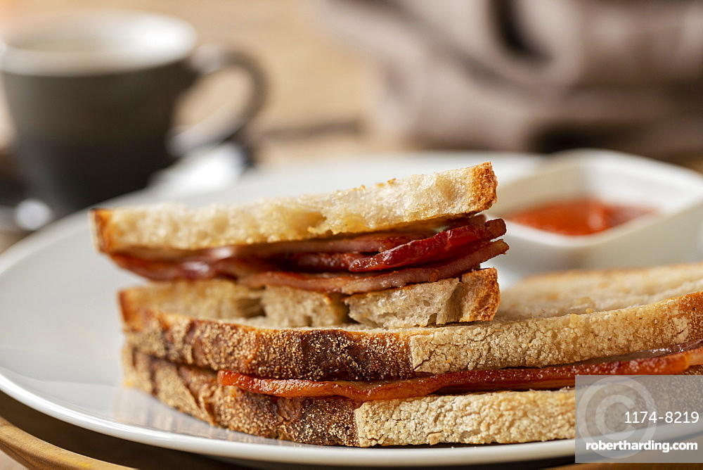 Close up of bacon sandwich and small bowl of home made tomato sauce in a cafe