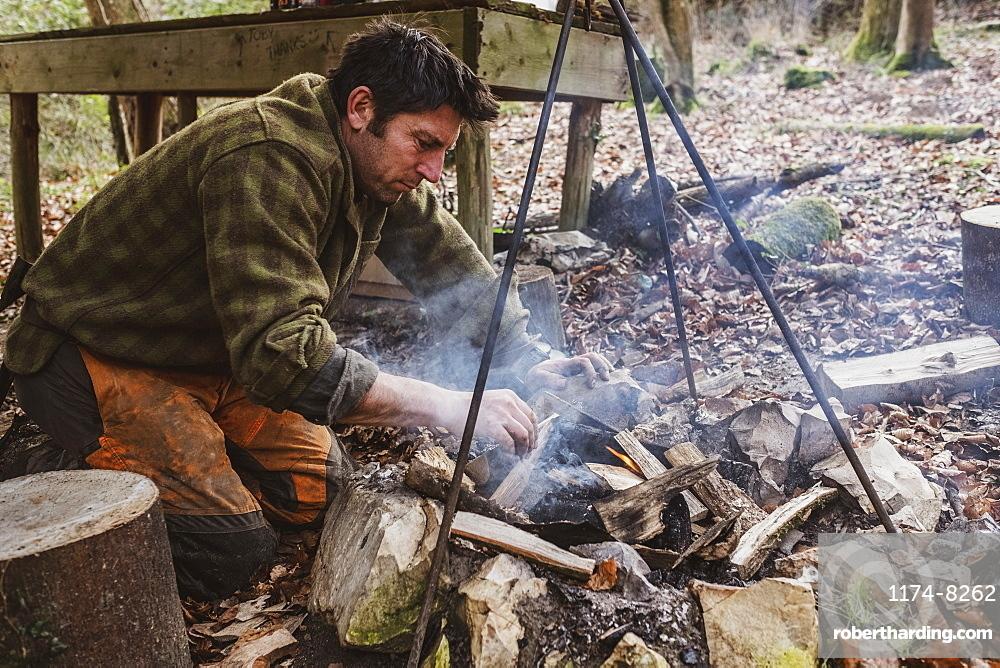 Man starting a camp fire in a forest, Devon, United Kingdom