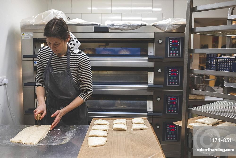 Artisan bakery making special sourdough bread, a baker cutting dough for buns