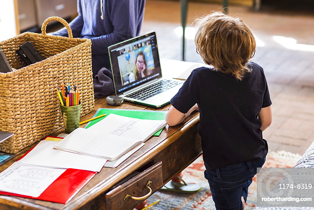 6 year old boy having a remote schooling session with his teacher